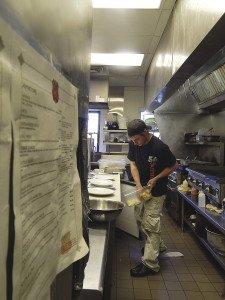 Carmody 61 head night cook Brian Godding preps burger plates. | KELSEY ROSETH