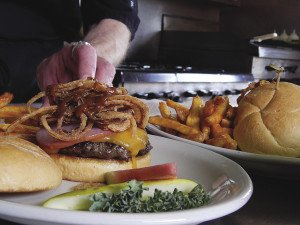 The Al Capone burger at Four Seasons in Finland is topped with Canadian bacon, cheddar cheese, onion straws and a whiskey steak sauce. | KELSEY ROSETH