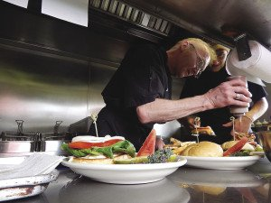 Chef Dan Morsette and cook Zach Morsette add the final touches to an order of burgers. | KELSEY ROSETH