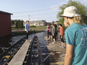 "Instructor Maddy Conklin briefs students about the ""barge,"" which is comprised of two boats rigged with a platform for the instructor between them. 