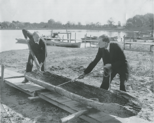 In August 1934, the Gunnarson family discovered a dugout canoe as they were extending their dock on North Arm Bay. The canoe has been dated to 1025-1165 A.D., making it the oldest dugout canoe found in Minnesota. Pictured here is G. A. and Helmer Gunnarson moving a canoe. | WESTERN HENNEPIN COUNTY PIONEER ASSOCIATION