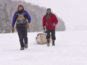 Amy and Dave Freeman haul their canoe down Newfound Lake at the end of Dec. as they prepare to swap their canoe for sled dogs and toboggans.