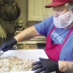 Shane Dickey of Superior Small Batch prepares vegan food at the community center in Finland.   SUBMITTED